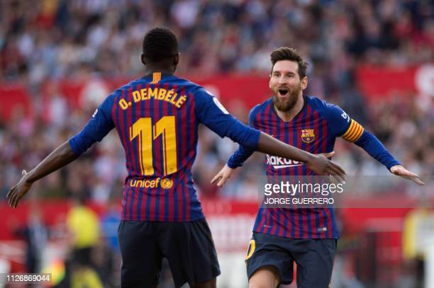 Barcelona's Argentinian forward Lionel Messi celebrates with Barcelona's French forward Ousmane Dembele after scoring a goal during the Spanish...