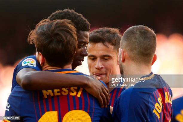 Barcelona's Argentinian forward Lionel Messi celebrates with Barcelona's French forward Ousmane Dembele Barcelona's Brazilian midfielder Philippe...