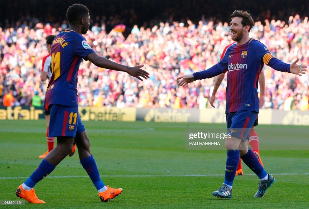 Barcelona's Argentinian forward Lionel Messi (R) celebrates with Barcelona's French forward Ousmane Dembele (L) after scoring during the Spanish League football match between FC Barcelona and Athletic Club Bilbao at the Camp Nou stadium in Barcelona on March 18, 2018. / AFP PHOTO / Pau Barrena