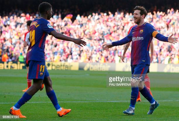 Barcelona's Argentinian forward Lionel Messi celebrates with Barcelona's French forward Ousmane Dembele after scoring during the Spanish League...