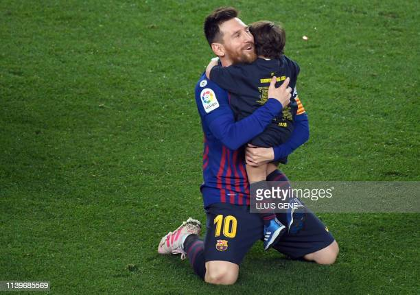 Barcelona's Argentinian forward Lionel Messi celebrates with his son becoming La Liga champions after winning the Spanish League football match...