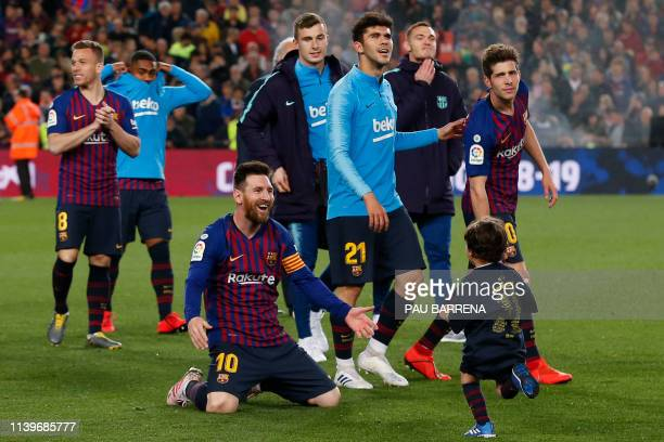 Barcelona's Argentinian forward Lionel Messi celebrates with one of his sons after Barcelona won their 26th league title at the end of the Spanish...