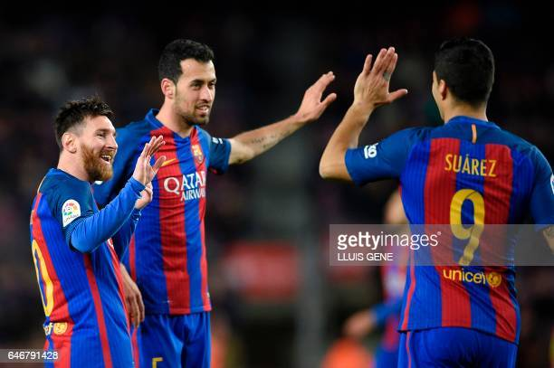 TOPSHOT Barcelona's Argentinian forward Lionel Messi celebrates with Barcelona's midfielder Sergio Busquets and Barcelona's Uruguayan forward Luis...
