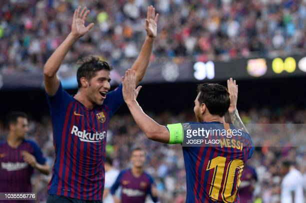 Barcelona's Argentinian forward Lionel Messi celebrates with Barcelona's Spanish midfielder Sergi Roberto after scoring during the UEFA Champions'...