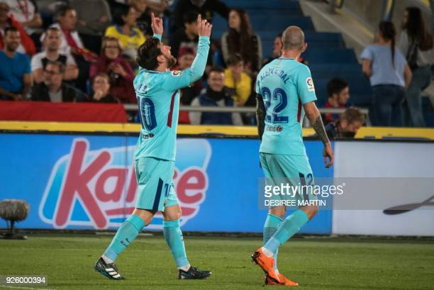 Barcelona's Argentinian forward Lionel Messi celebrates with Barcelona's Spanish midfielder Aleix Vidal after scoring during the Spanish league...