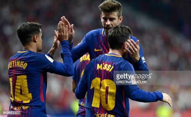 Barcelona's Argentinian forward Lionel Messi celebrates with Barcelona's Spanish defender Gerard Pique and Barcelona's Brazilian midfielder Philippe...