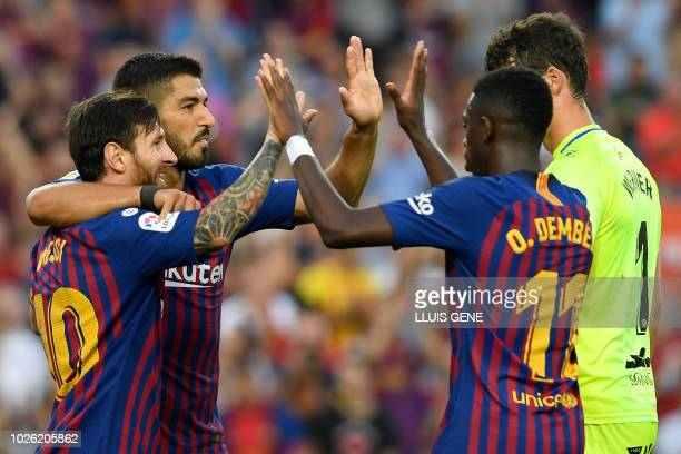 TOPSHOT Barcelona's Argentinian forward Lionel Messi celebrates with teammates scoring his team's sixth goal with Barcelona's Uruguayan forward Luis...