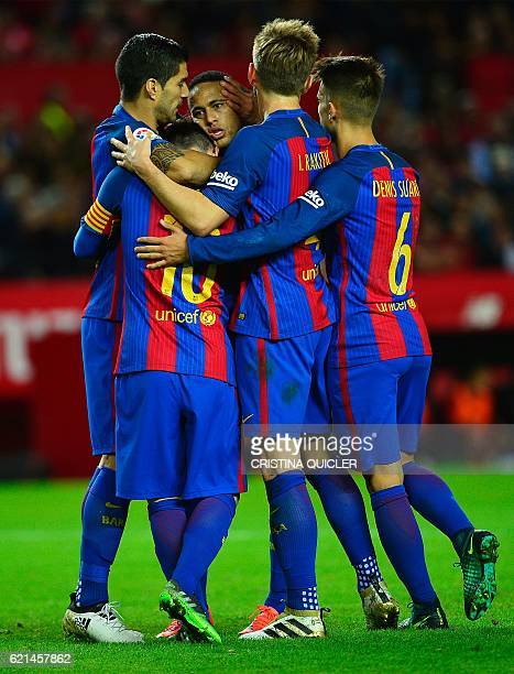 Barcelona's Argentinian forward Lionel Messi celebrates with teammates after scoring during the Spanish league football match Sevilla FC vs FC...