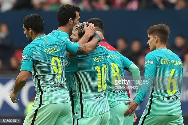Barcelona's Argentinian forward Lionel Messi celebrates with teammates during the Spanish league football match CA Osasuna vs FC Barcelona at the...