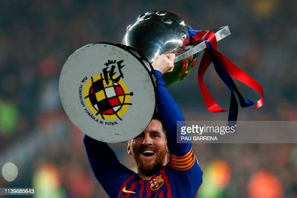 Barcelona's Argentinian forward Lionel Messi celebrates with the Liga trophy as Barcelona won their 26th league title after the Spanish League...