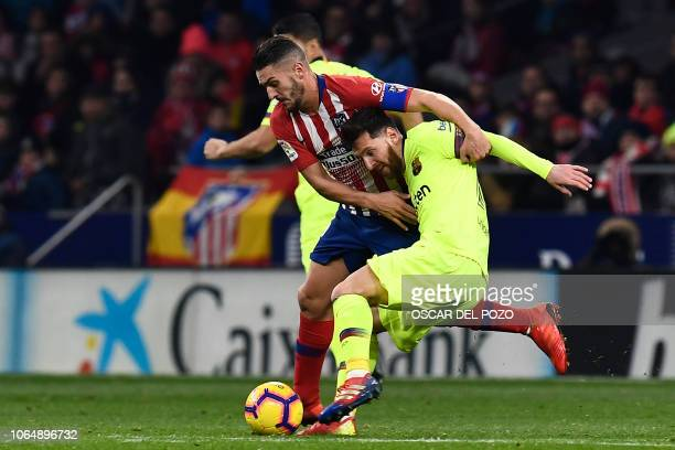 Barcelona's Argentinian forward Lionel Messi challenges Atletico Madrid's Spanish midfielder Koke during the Spanish league football match between...