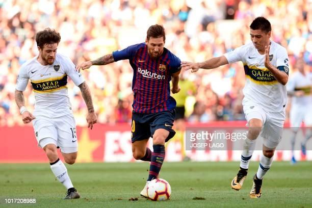 TOPSHOT Barcelona's Argentinian forward Lionel Messi challenges Boca Juniors' Uruguayan midfielder Nahitan Nandez and Boca Juniors' Argentinian...