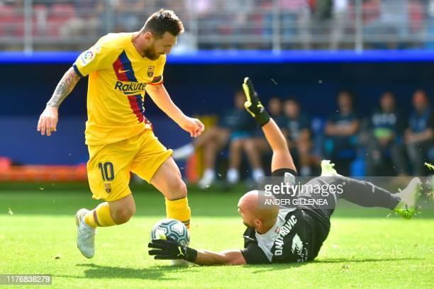 Barcelona's Argentinian forward Lionel Messi challenges Eibar's Portuguese Serbian goalkeeper Marko Dmitrovic during the Spanish league football...