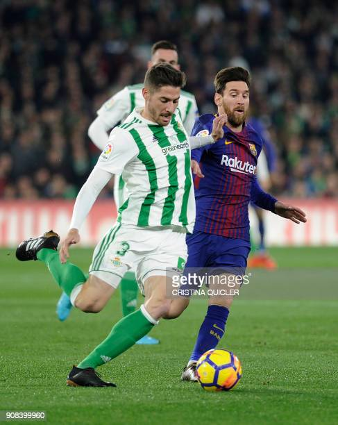 Barcelona's Argentinian forward Lionel Messi challenges Real Betis' Spanish midfielder Javi Garcia during the Spanish league football match between...