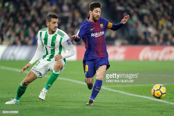 Barcelona's Argentinian forward Lionel Messi challenges Real Betis' Moroccan defender Zou during the Spanish league football match between Real Betis...