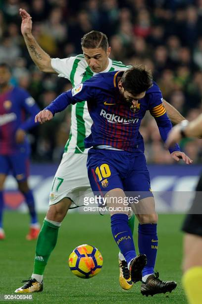Barcelona's Argentinian forward Lionel Messi challenges Real Betis' Spanish midfielder Joaquin during the Spanish league football match between Real...