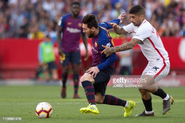 Barcelona's Argentinian forward Lionel Messi challenges Sevilla's Argentinian midfielder Ever Banega during the Spanish league football match between...