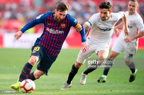 Barcelona's Argentinian forward Lionel Messi challenges Sevilla's Spanish midfielder Jesus Navas during the Spanish league football match between...