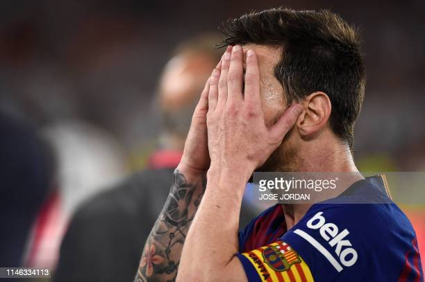 Barcelona's Argentinian forward Lionel Messi covers his face at the end of the 2019 Spanish Copa del Rey final football match between Barcelona and...