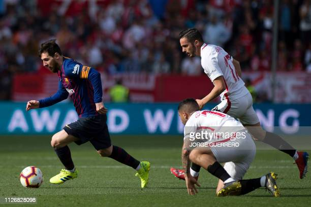 Barcelona's Argentinian forward Lionel Messi dribbles the ball ahead of Sevilla's Argentinian midfielder Ever Banega and Sevilla's Spanish midfielder...