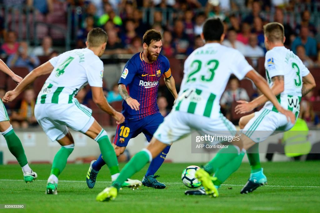 Barcelona's Argentinian forward Lionel Messi (C) faces several Betis players during the Spanish league footbal match FC Barcelona vs Real Betis at the Camp Nou stadium in Barcelona on August 20, 2017. / AFP PHOTO / Josep LAGO