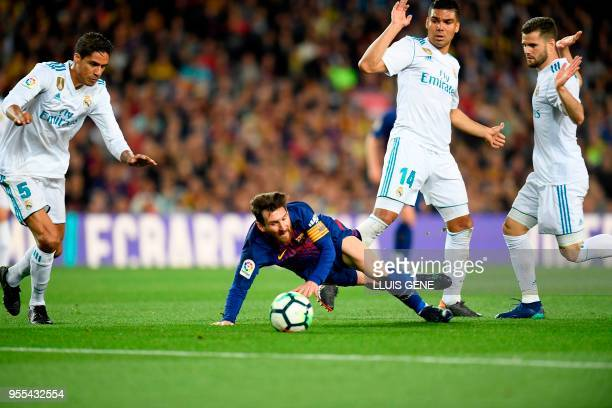 TOPSHOT Barcelona's Argentinian forward Lionel Messi falls as he challenges Real Madrid's French defender Raphael Varane Real Madrid's Brazilian...