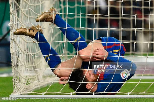 Barcelona's Argentinian forward Lionel Messi falls down under the net of Real Sociedad's goal during the Spanish league football match FC Barcelona...