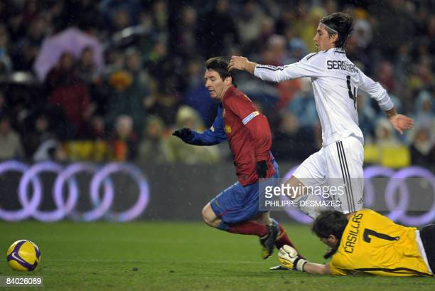 Barcelona's Argentinian forward Lionel Messi fights for the ball with Real Madrid's goalkeeper Iker Casillas and defender Sergio Ramos during their...