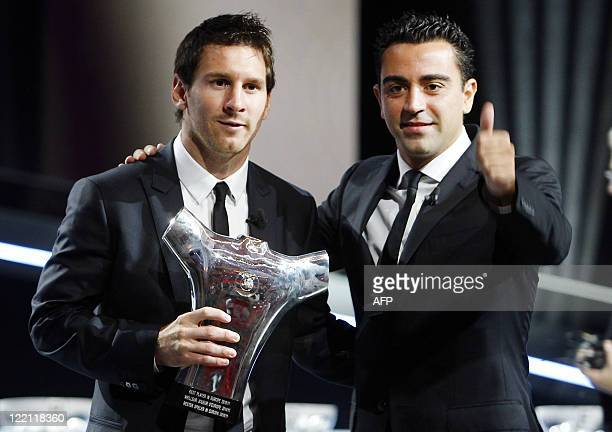FC Barcelona's Argentinian forward Lionel Messi flanked by FC Barcelona's Spanish midfielder Xavi Hernandez poses with his trophy for football's Best...