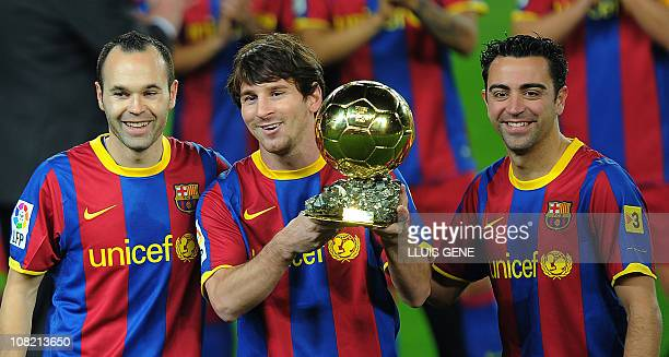 Barcelona's Argentinian forward Lionel Messi flanked with Barcelona's midfielder Xavi Hernandez and Barcelona's midfielder Andres Iniesta poses with...
