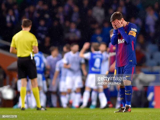 Barcelona's Argentinian forward Lionel Messi gestures as Real Sociedad players celebrate their opening goal during the Spanish league football match...