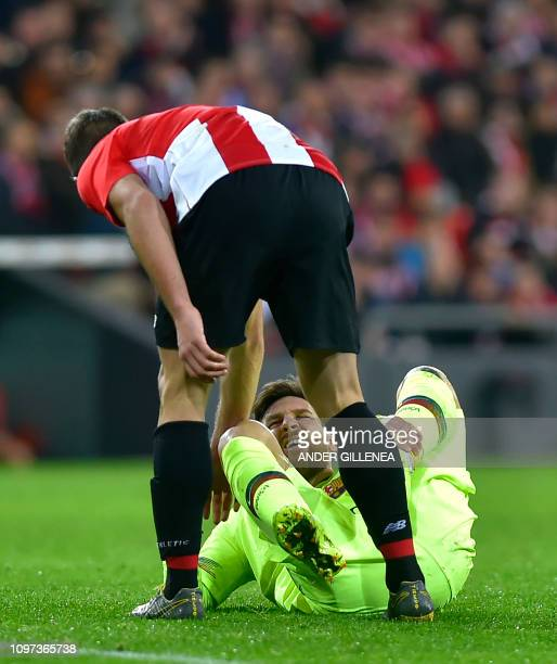 Barcelona's Argentinian forward Lionel Messi gestures in pain next to Athletic Bilbao's Spanish defender Yeray Alvarez during the Spanish league...