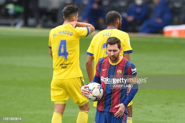 Barcelona's Argentinian forward Lionel Messi grabs the ball during the Spanish league football match between FC Barcelona and Cadiz CF at the Camp...