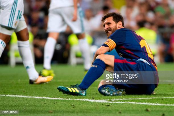 Barcelona's Argentinian forward Lionel Messi grimaces as he sits on the ground during the second leg of the Spanish Supercup football match Real...
