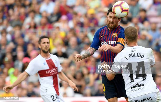 Barcelona's Argentinian forward Lionel Messi heads the ball beside SD Huesca's Spanish defender Jorge Pulido during the Spanish league football match...