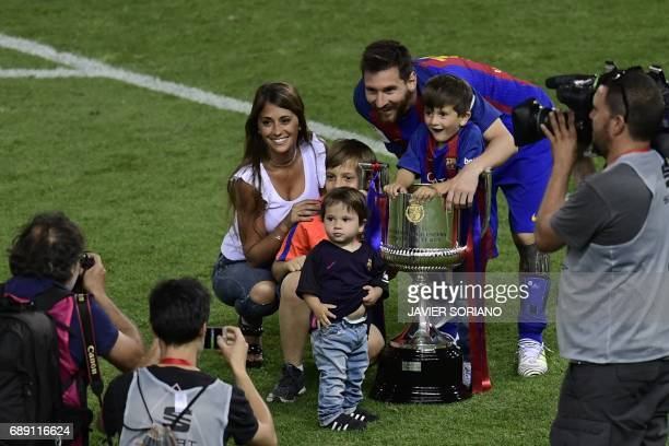 TOPSHOT Barcelona's Argentinian forward Lionel Messi his wife Antonella Roccuzzo and sons pose with the trophy at the end of the Spanish Copa del Rey...