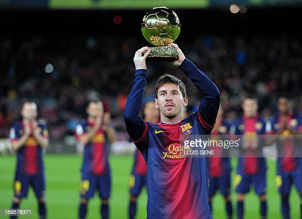 Barcelona's Argentinian forward Lionel Messi holds his 4th FIFA Ballon d'Or trophy prior to the Spanish Copa del Rey quarterfinal football match FC...