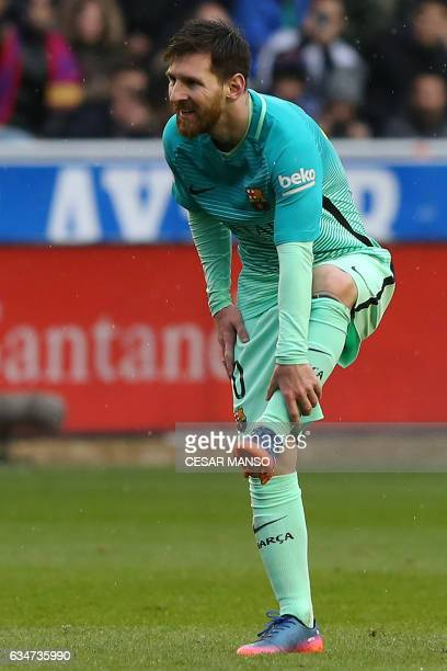 Barcelona's Argentinian forward Lionel Messi holds his shin during the Spanish league football match Deportivo Alaves vs FC Barcelona at the...