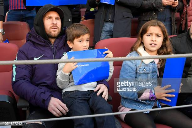 Barcelona's Argentinian forward Lionel Messi holds his son as they sit on the grandsatands during the Spanish league football match between FC...