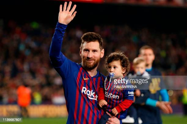 Barcelona's Argentinian forward Lionel Messi holds his son Ciro as he celebrates after Barcelona won their 26th league title at the end of the...