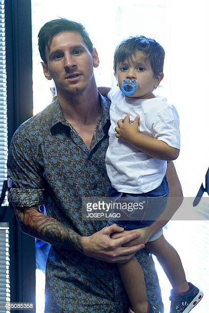 Barcelona's Argentinian forward Lionel Messi holds his son Thiago as they arrive to a farewell press conference for Barcelona's former forward Pedro...