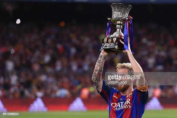 Barcelona's Argentinian forward Lionel Messi holds the Spanish Supercup trophy after winning after winning the second leg of the Spanish Supercup...