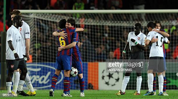 Barcelona's Argentinian forward Lionel Messi hugs teammate Xavi Hernandez at the end of the game against Arsenal during the Champions League...