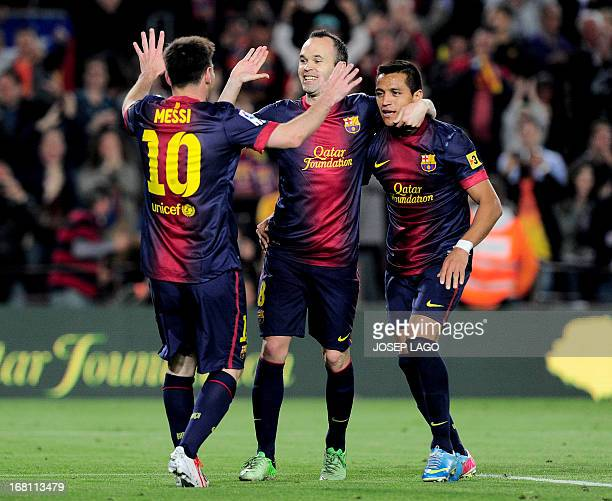 Barcelona's Argentinian forward Lionel Messi is congratulated by his teammates Barcelona's midfielder Andres Iniesta and Barcelona's Chilean forward...
