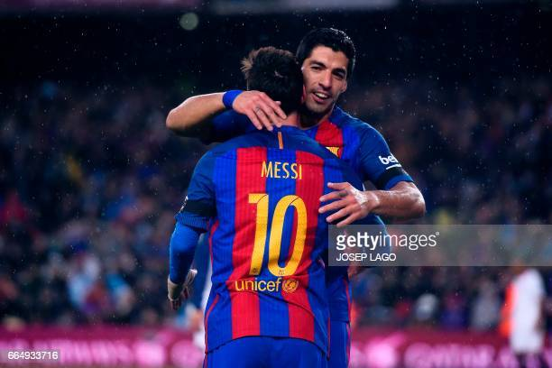Barcelona's Argentinian forward Lionel Messi is congratulated by his teammate Barcelona's Uruguayan forward Luis Suarez after scoring during the...