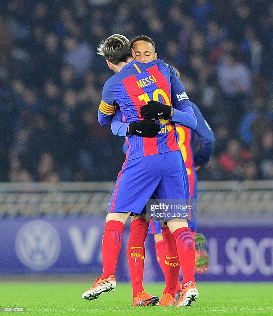 TOPSHOT - Barcelona's Argentinian forward Lionel Messi (L) is congratulated by teammate Brazilian forward Neymar da Silva Santos Junior (R) after scoring his team's first goal during the Spanish league football match Real Sociedad vs FC Barcelona at the Anoeta stadium in San Sebastian, on November 27, 2016. / AFP / ANDER