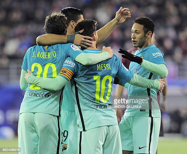 Barcelona's Argentinian forward Lionel Messi is congratulated by Barcelona's Brazilian forward Neymar and teammates after scoring their second goal...