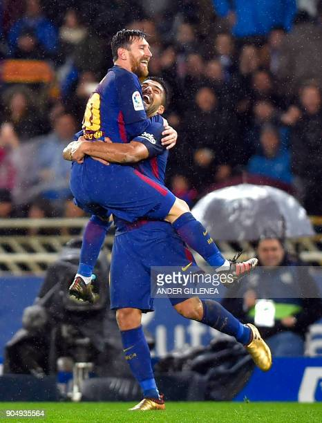 Barcelona's Argentinian forward Lionel Messi is congratulated by teammate Uruguayan forward Luis Suarez after scoring their team's fourth goal during...