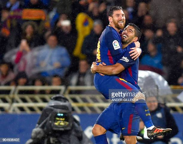 TOPSHOT Barcelona's Argentinian forward Lionel Messi is congratulated by teammate Uruguayan forward Luis Suarez after scoring their team's fourth...