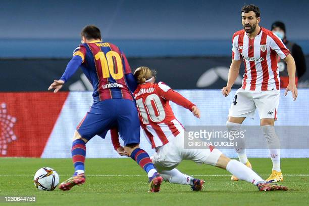 Barcelona's Argentinian forward Lionel Messi is fouled by Athletic Bilbao's Spanish forward Iker Muniain during the Spanish Super Cup final football...